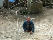 An old man weaving bamboo containers